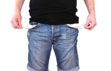 Person with no money showing empty pockets