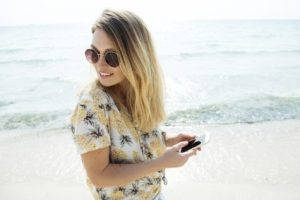 Woman looking at her smartphone at the beach