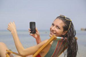 Woman using phone at beach