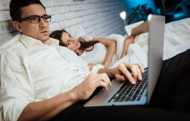 Man working on computer in bed with wife