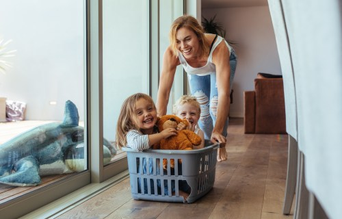 Mother playing with her children in laundry basket