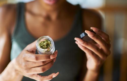 Woman opening jar of medical marijuana
