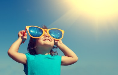 Happy little girl with big sunglasses looking at the sunshine