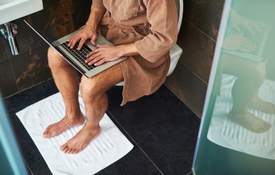 Man in bathrobe using laptop while sitting on toilet at home