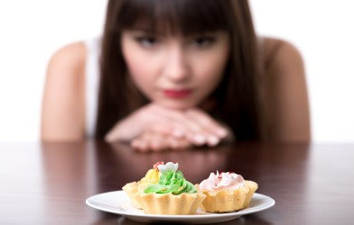 Self-control: Woman resisting temptation to eat cake