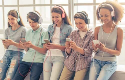 Teens, children using smartphones listening to music