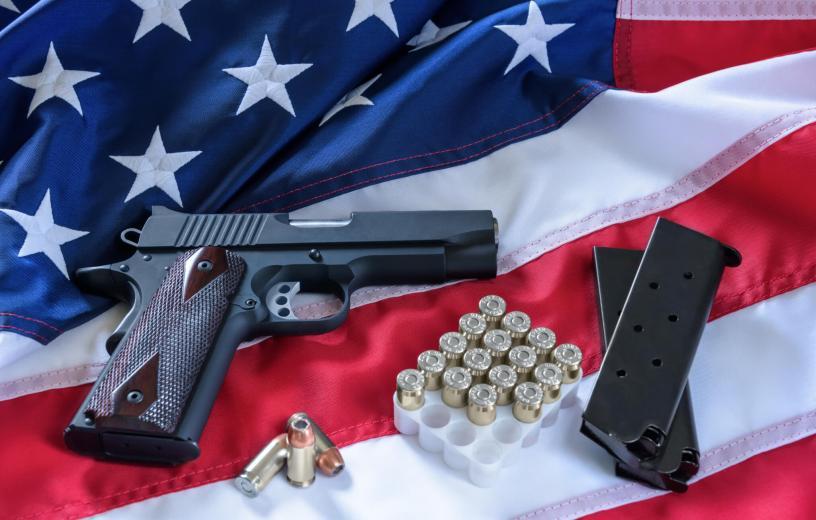 Gun with ammo on an American flag: gun control and gun rights debate