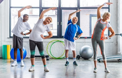 Seniors, older adults enjoying exercise class at gym