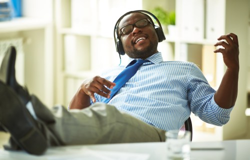 Man listening to music, getting distracted at work