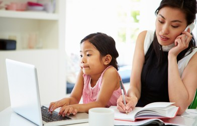 Busy mom working on phone while child plays on computer