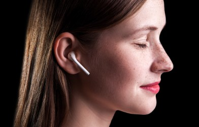 Woman listening to wireless earphones, doing mindfulness meditation