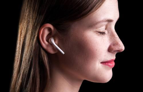 Woman listening to wireless earphones, doing mindfulness meditation