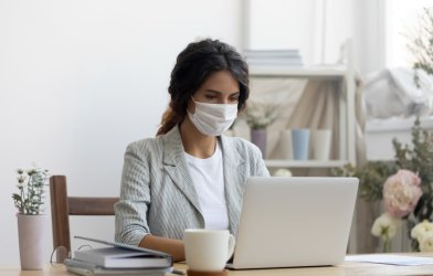 Woman wearing face mask while working during coronavirus outbreak