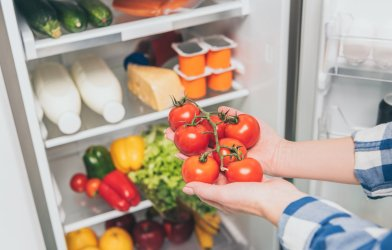 Woman holding tomatoes in front of refrigerator