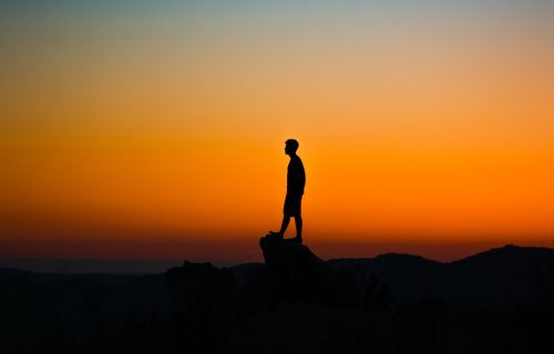 Person alone on cliff at sunset