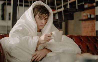 Sick man covering himself with blanket, drinking tea