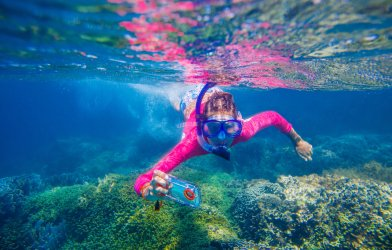 Girl or woman scuba diving with smartphone, taking selfie or streaming video underwater