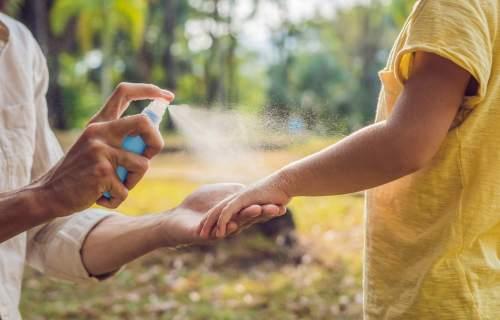 Parent spraying bug spray on child