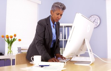Older Black woman working at desk in office