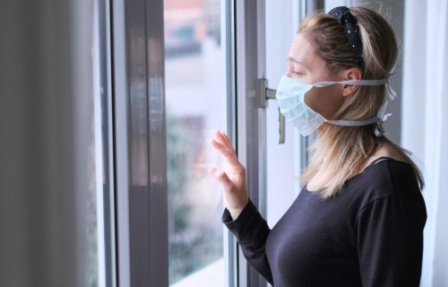 Woman wearing mask looking out window while under quarantine isolation for coronavirus / COVID-19 outbreak