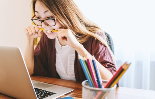 College student stress: Woman biting pencil while doing work on computer