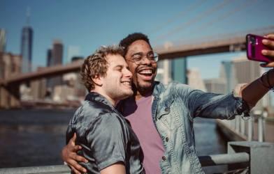 Men, couple taking selfie together