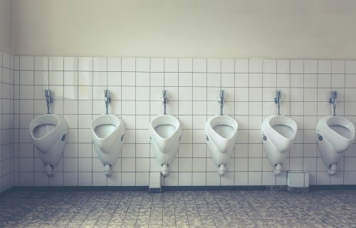 Row of urinals, toilets in bathroom