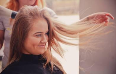Woman getting a haircut, having her hair blown out