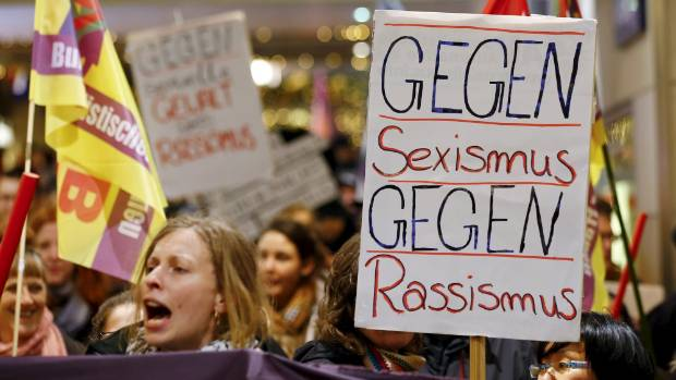 """Women shout slogans and hold up a placard that reads """"Against Sexism - Against Racism"""" as they march through Cologne."""