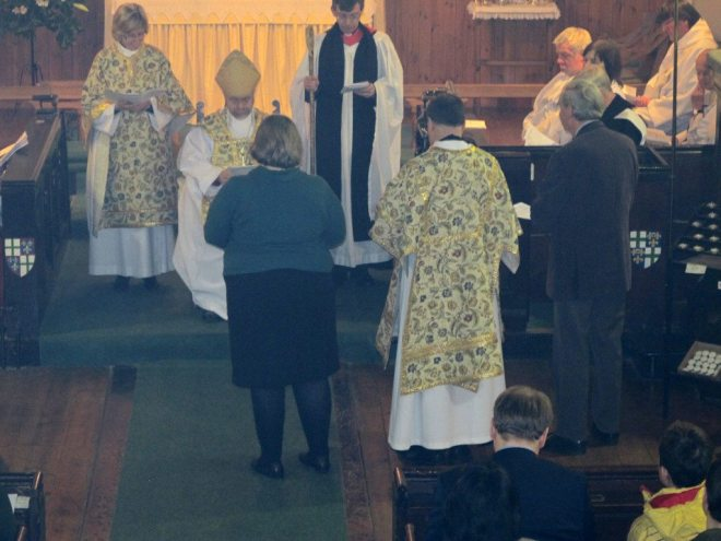 The Vestry Secretary, Bridget Campbell,  (left) and Treasurer, Michael Paulson-Ellis, (right) present Canon Allan Maclean to the Bishop of Edinburgh at his Institution on St Vincent's Day, 22 January 2015