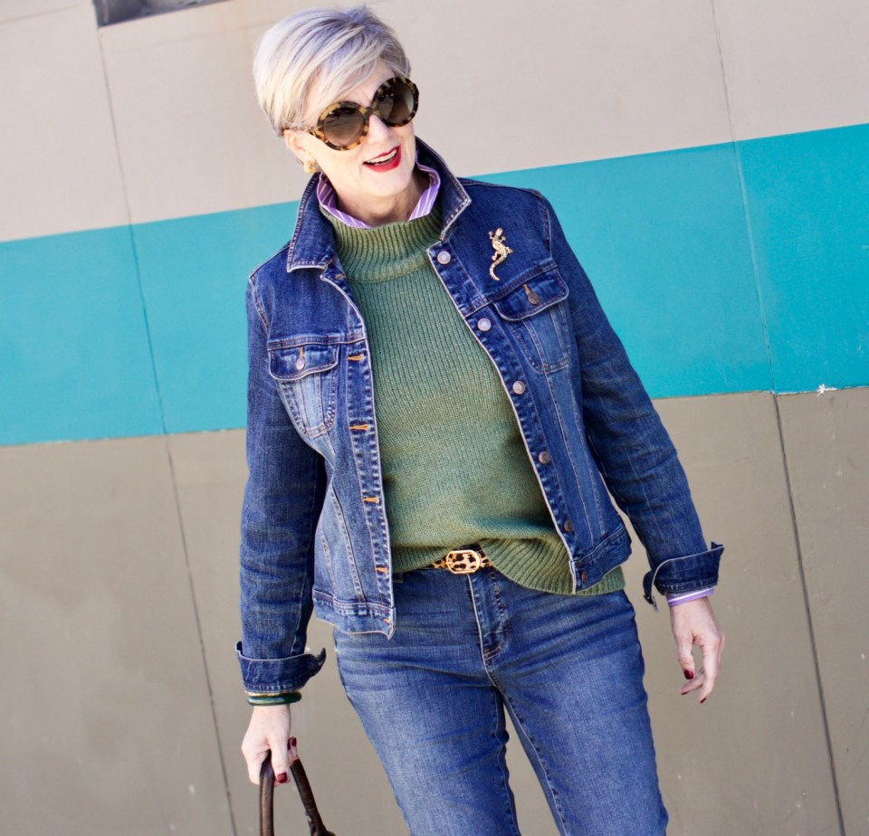 beth from Style at a Certain Age wears a chunky turtleneck layered over a stripe button down, skinny ankle jeans, a denim jacket, and booties
