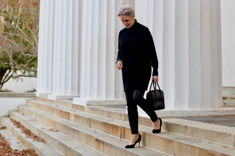 beth from Style at a Certain Age wears a black cashmere Turtleneck dress, faux leather leggings and suede pumps.