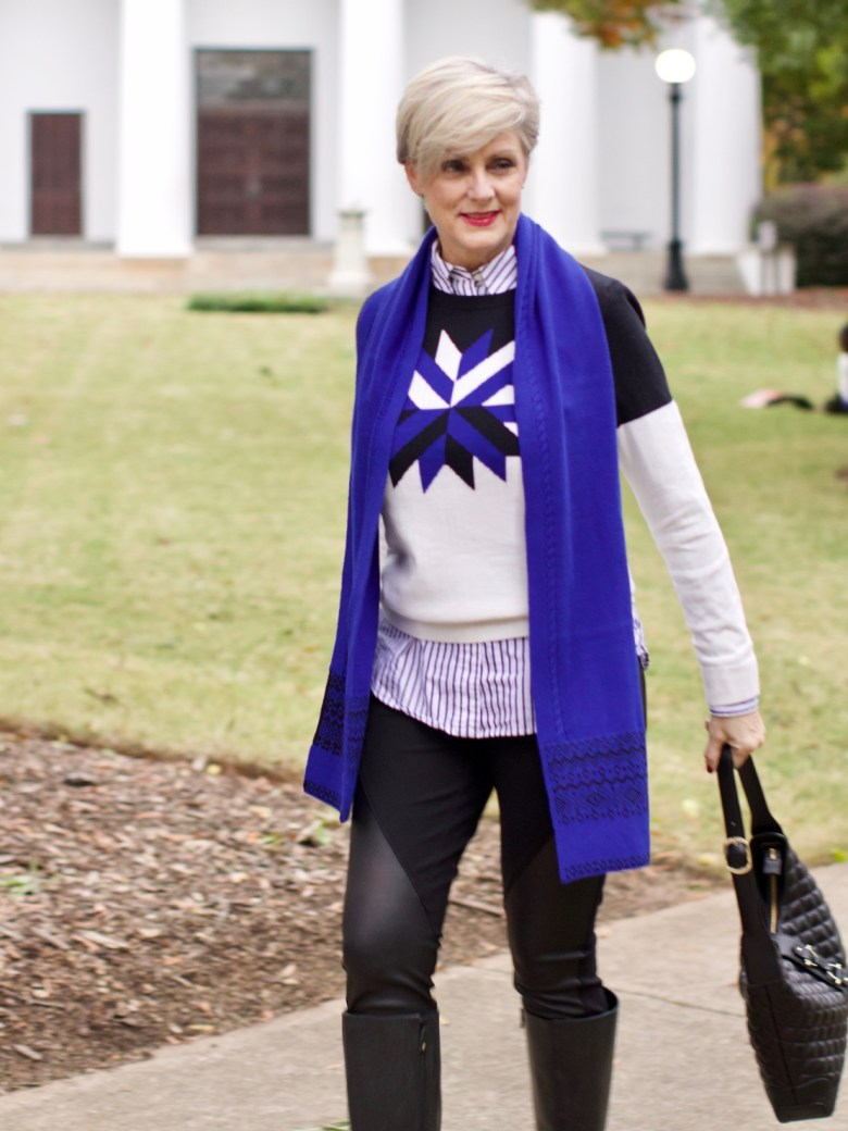 beth from Style at a Certain Age wears a snowflake intarsia sweater, DKNY ponte leggings, striped shirt, riding boots, and a cobalt blue intarsia trim scarf