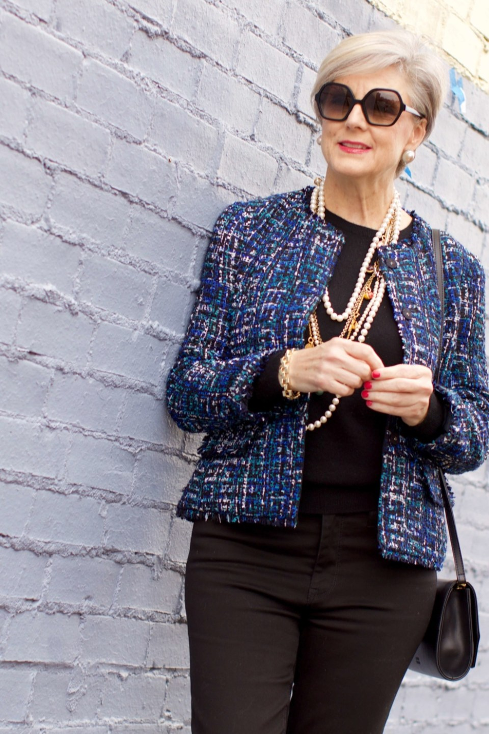 beth at Style at a Certain Age wears an Ann Taylor tweed military jacket, Everlane crewneck cashmere, J.Crew cropped flare denim, pointy-toed boots and strings of pearls