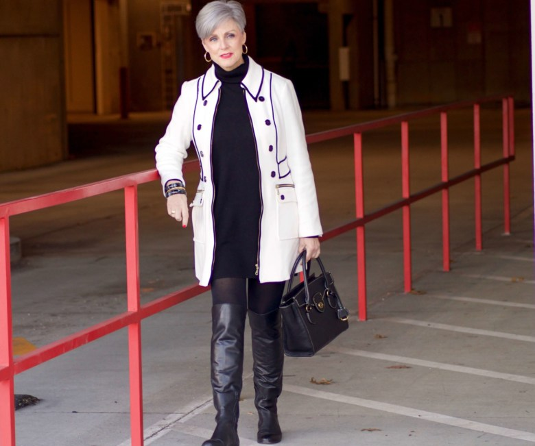 beth from Style at a Certain Age wears a cashmere turtleneck dress, black over the knee boots, and ivory and black coat