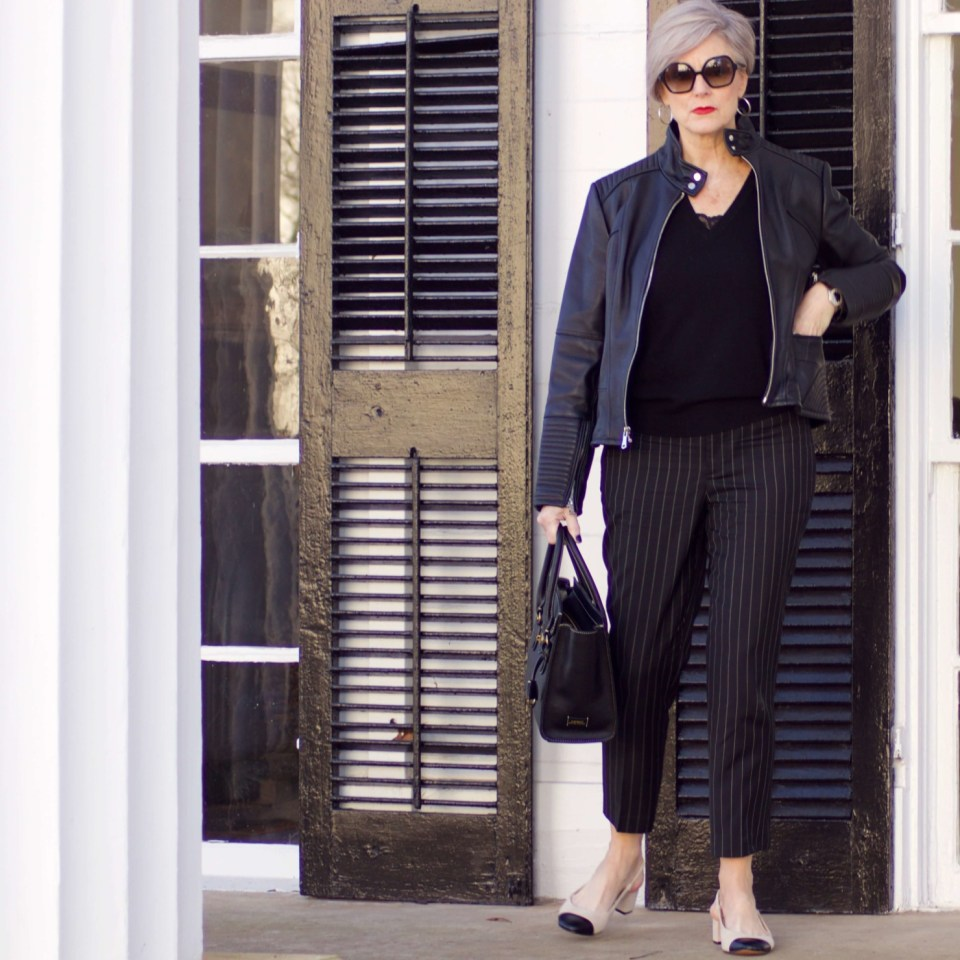 beth from Style at a Certain Age wears Ralph Lauren pinstripe pants, Everlane cashmere sweater, black leather moto jacket, and cap toe slingbacks
