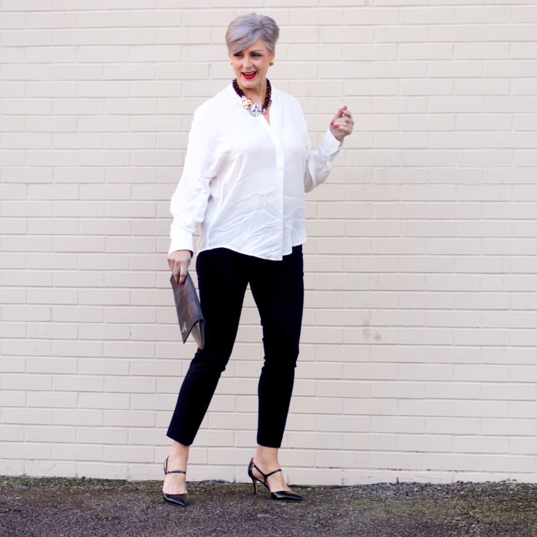 beth from Style at a Certain Age wears an ivory Vince jacquard silk blouse, Everlance slim wool pant, and SJP mary jane patent leather shoes