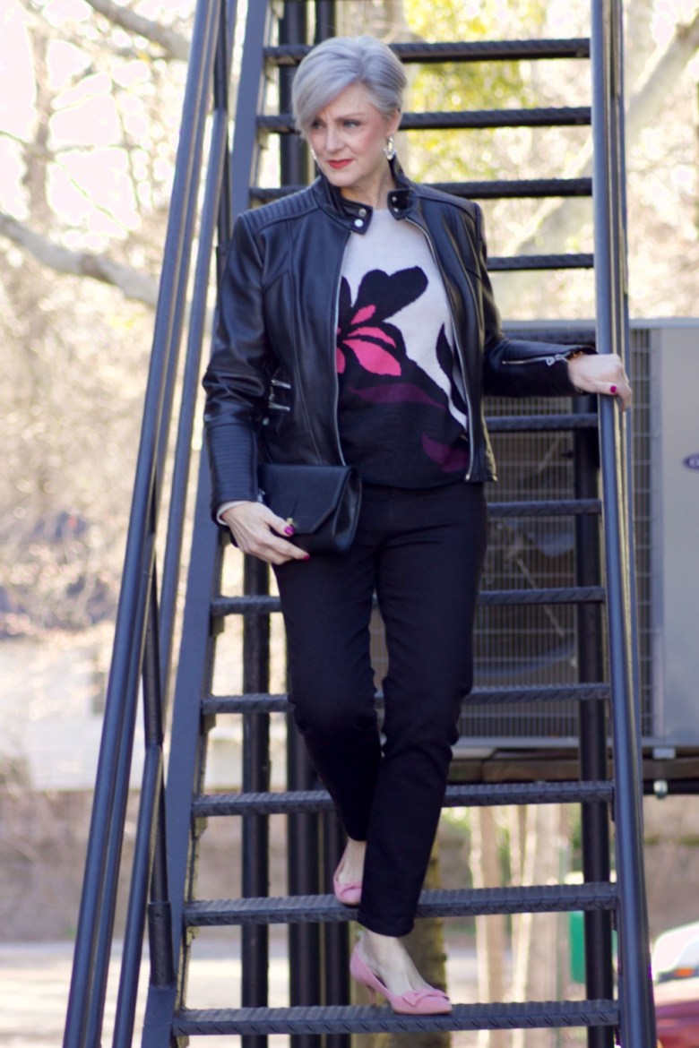 beth from Style at a Certain Age wears a floral jacquard sweater, black skinny jeans, black leather moto jacket and pink suede pumps for date night