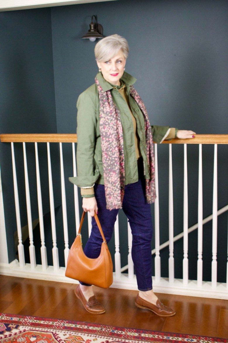 beth from Style at a Certain Age wears a ruffleneck sweater, skinny jeans, green utility jacket, hobo handbag, and loafers