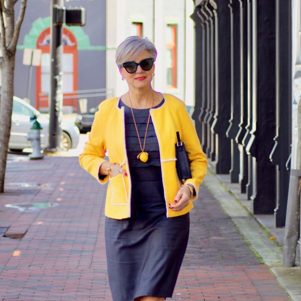 beth from Style at a Certain Age wears a navy blue sheath dress, Boden yellow jacket, navy suede shoes, Tory Burch lemon locket
