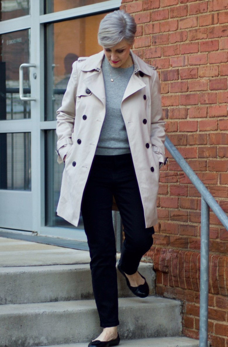beth from Style at a Certain Age wears an Everlane grey cashmere crewneck, high rise black cigarette jean, Tory Burch black ballet flats and a double-breasted trench coat
