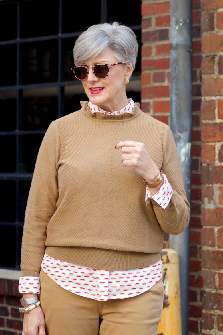 beth from Style at a Certain Age wears a J.Crew camel ruffle neck sweater, slim boy chinos and a Boden modern classic shirt with a bold print.