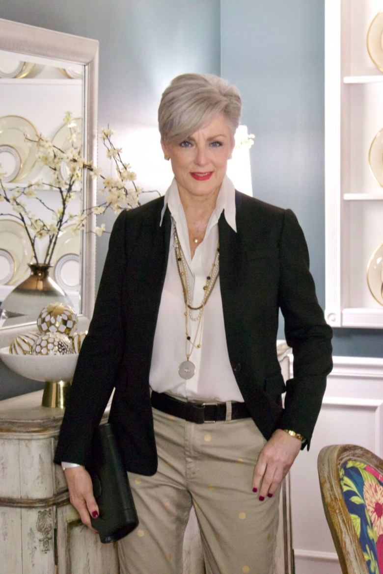 beth from Style at a Certain Age wears J.Crew chinos, black blazer, ivory silk blouse, black pumps and black clutch handbag