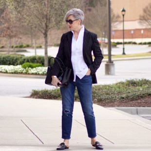 beth from Style at a Certain Age travels in style in a pinstripe blazer, white button down, blue jeans, and black slides