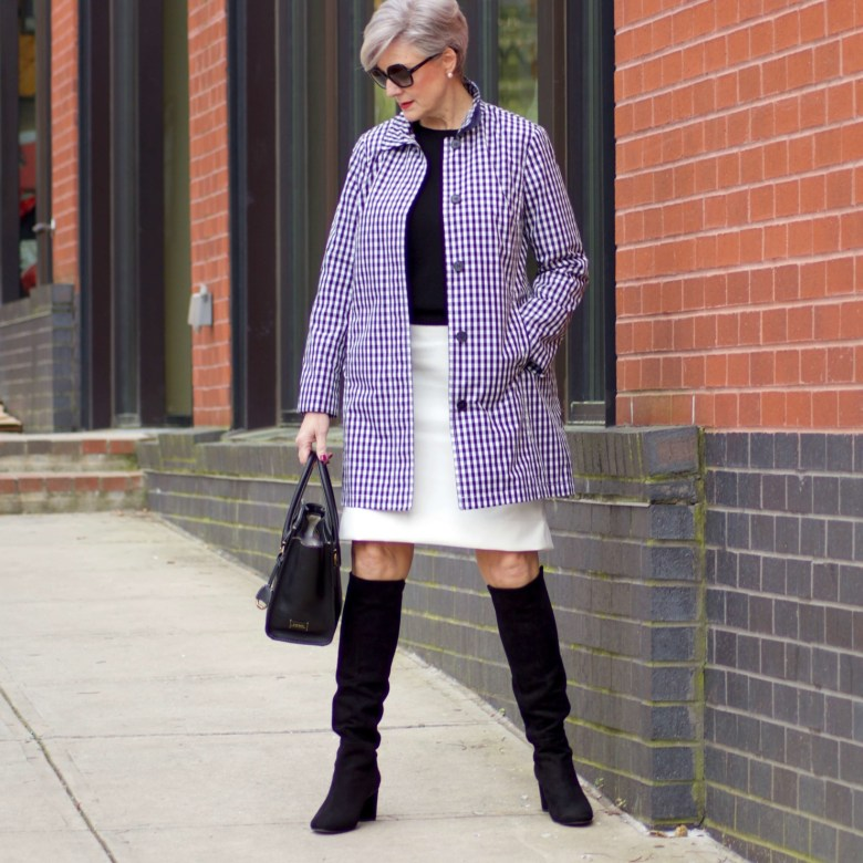 beth from Style at a Certain Age wears a gingham raincoat, white skirt, black sweater, and black boots