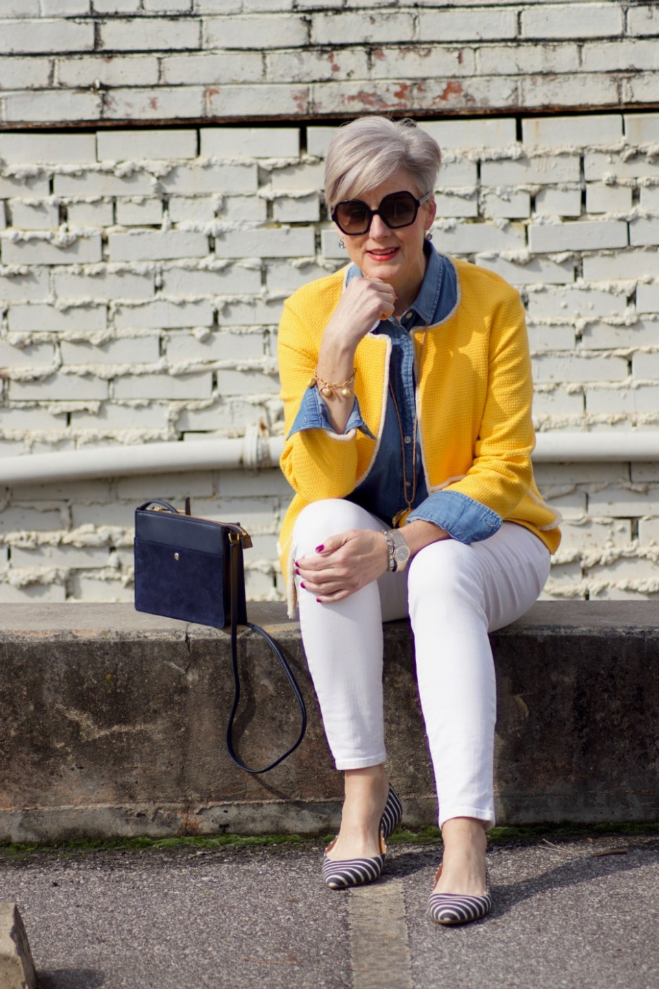 beth from Style at a Certain Age wears a Boden yellow blazer, chambray shirt, white denim and striped shoes