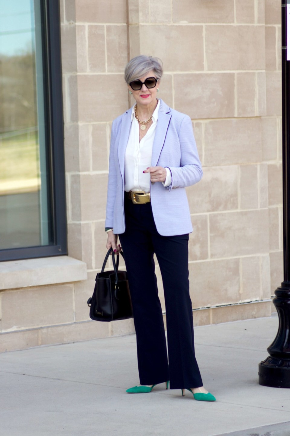 beth from Style at a Certain Age wears a Ann Taylor green trench coat, navy trousers, white essential shirt, knit striped blazer, and green suede pumps.