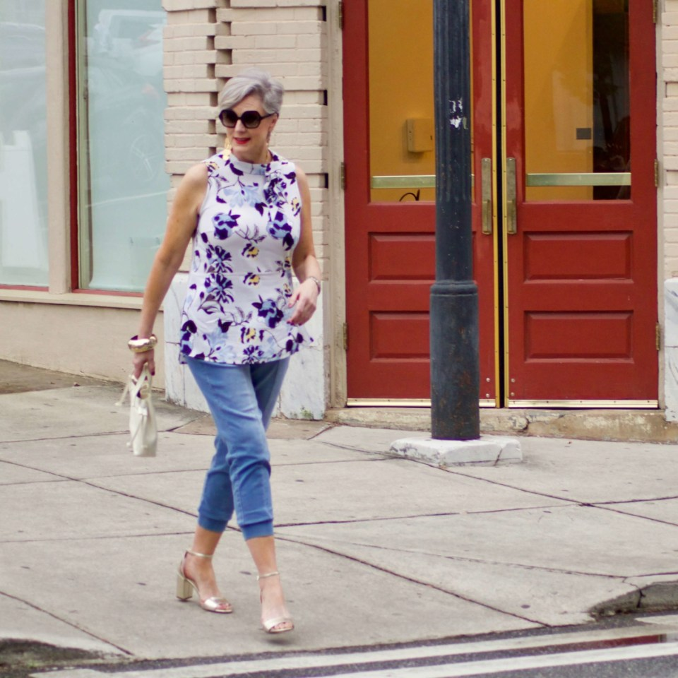 beth from Style at a Certain Age wears a floral top, denim joggers, gold metallic block sandals, and carries a drawstring crossbody handbag. Walmart we dress America