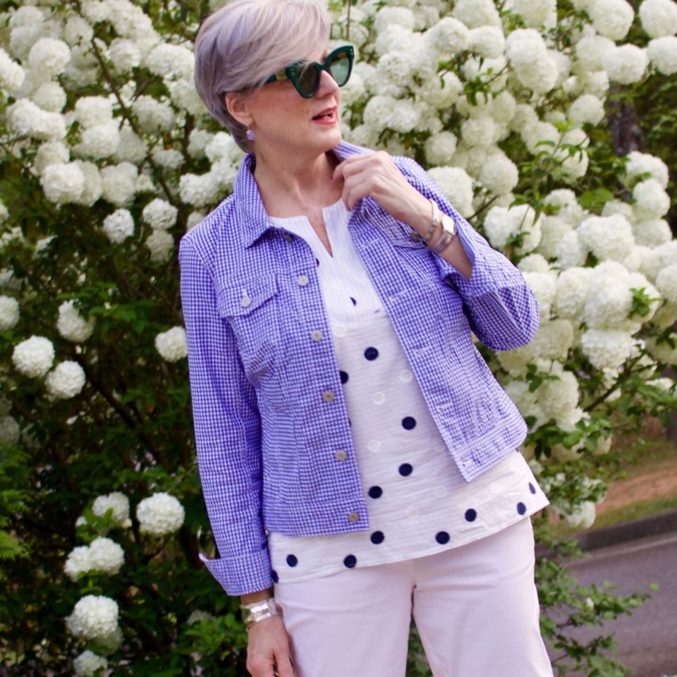 beth from Style at a Certain Age wears a gingham jean jacket, polka dot top, white chinos and wicker handbag