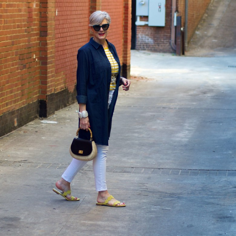 beth from Style at a Certain Age wears a denim duster, striped tee, white denim, suede sandals and wicker handbag